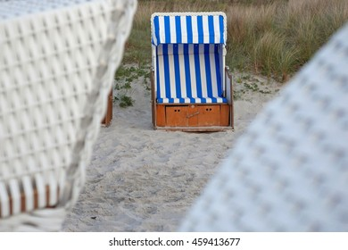 Blue and white striped roofed wicker beach chair in Zingst at the Baltic Sea, Germany
