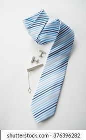 Blue and white striped tie with cufflinks, isolated on white background businessman