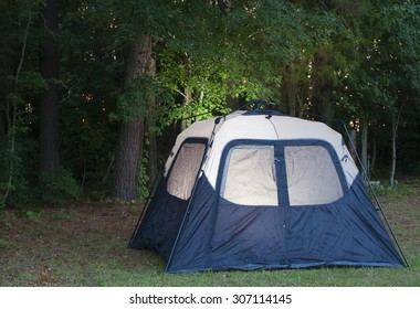 Blue and white tent with a light on inside and toward the forest