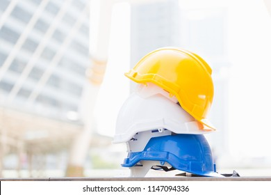 Blue, white, and yellow hard safety helmet hat for safety project on the big building in city / Safety first concept.