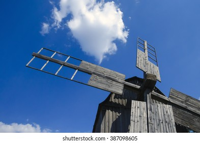 blue windmill old. Old wooden windmill on the blue sky background