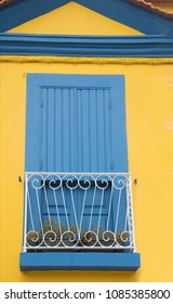 Blue window against a yellow wall