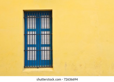 Blue window and bright yellow wall in old city of Havana, Cuba