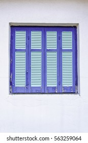 Blue window on white background. Closed blinds, greek style.