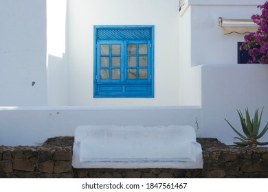 Blue window, white building, flowers and a stone bench. Mediterran Setting
