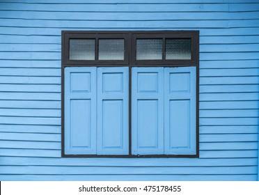 Blue windows on blue wooden wall