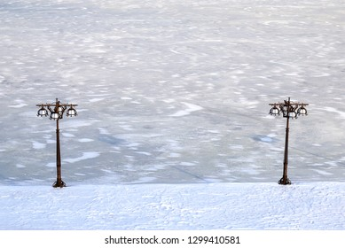 Blue winter cityscape of a river covered with ice, snow. and embankment with vintage metal lantern, Dnepropetrovsk, Dnipro city , Ukraine,
