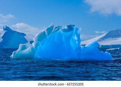 Blue in blue. Wonderful transparent iceberg in Antarctica
