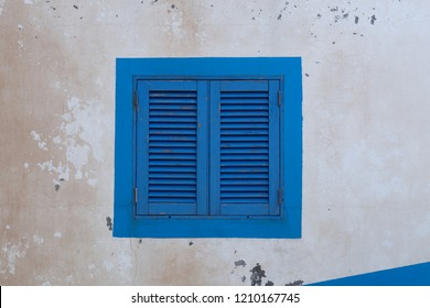 Blue wood window on an old dirty wall. Funchal, Madeira island, Portugal