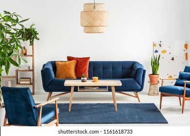 Blue wooden armchairs and couch in living room interior with plants and lamp above table. Real photo