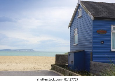 A blue wooden beach hut with a coastal view looking towards the needles of the isle of wight. Location in Christchurch, Dorset UK.