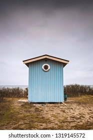 Blue wooden beach hut. Viken, Sweden.