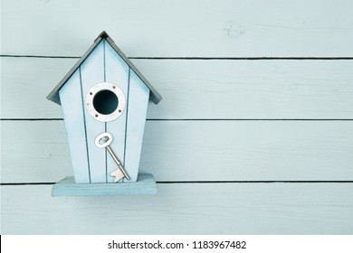 Blue wooden bird house with a metal key on a blue wooden background with copy space as a concept for a new home