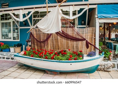 Blue wooden boat on the coast, which serves as a decoration in a cafe with flowers, and other details