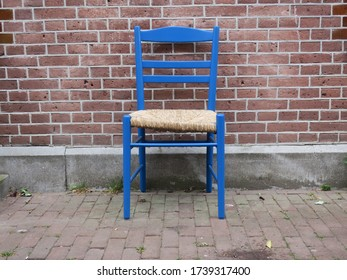 a blue wooden chair  on the sidewalk in front of a red brick wall