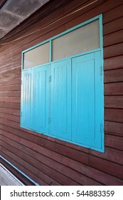 Blue wooden closed windows with red brown wooden wall. Vintage style of Thailand windows