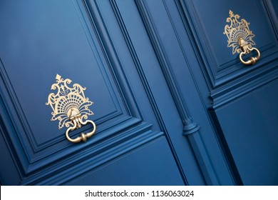 Blue wooden door and bronze knockers