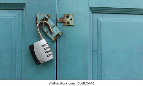 blue wooden door with an unlocked lock white key