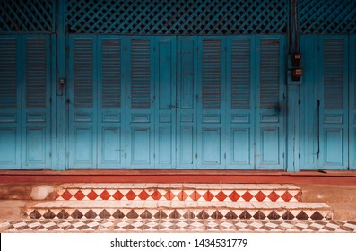 Blue wooden doors of French Colonial building with retro ceramic tiles floor steps - Famous old historic attraction and photo spot - Luang Prabang, Laos