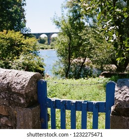 Blue wooden fence with bridge in background