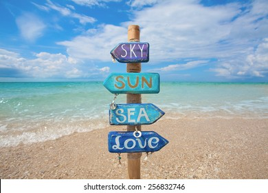 """Blue wooden handmade signpost decorated with sea shells with the inscription """"sky, sun, sea, love"""" on tropic beach in Thailand."""