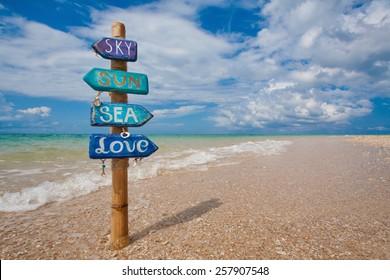 Blue wooden handmade signpost on the tropic beach.