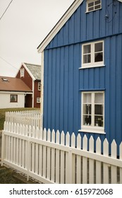 Blue wooden house behind a white fence
