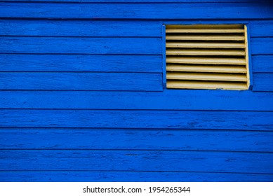 blue wooden hut with a yellow louvred window