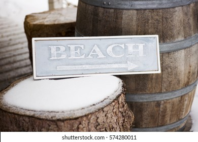 blue wooden sign on tree stump with the word Beach written on it