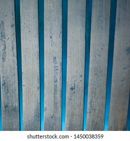 Blue wooden stakes with a bright blue background, vertical lines with an antique texture and blue paint chipping off of the wood.