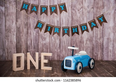 Blue wooden toy car on a wooden background. Decorative zone The first year.