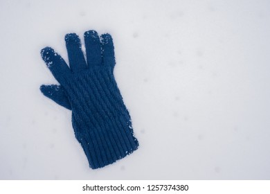Blue wool gloves in the snow