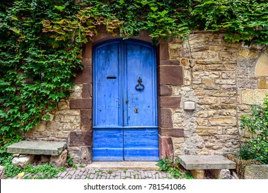 A blue and worn door with green ivy above on the stone walls of a small town in French countryside