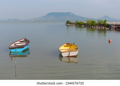 Blue and yellow boats on lake Balaton with the Badacsony mountain in the background in Hungary.