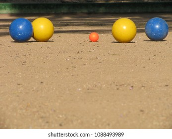 Blue and yellow bocce balls on a traditional court surround the pallino or jack in the traditional Italian version of the international bowling game.