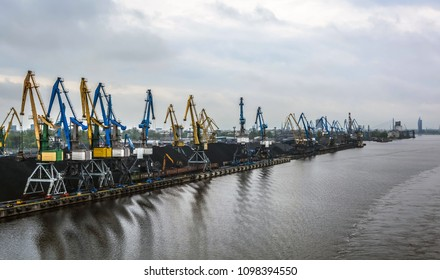 Blue and yellow cranes in cargo port transporting coal. Industrial scene.