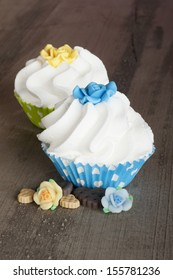blue and yellow cupcake with whipped cream on a wooden table