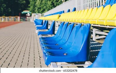 Blue and yellow empty stadium seats in school