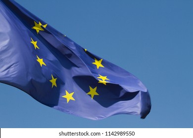 Blue and yellow flag of the European Union, blowing in the breeze.
