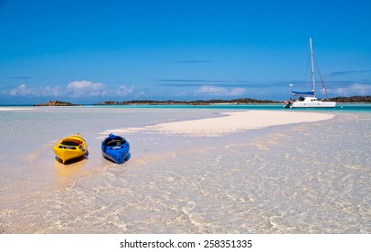 blue and yellow kayaks beached along the white sand with catamaran sailboat anchored in the background.