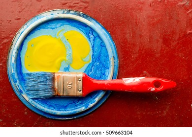 Blue and yellow paint with paint brush over red background