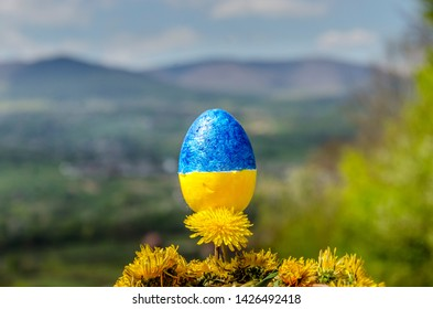 Blue and yellow painted Easter egg on dandelions and blurred mountain background