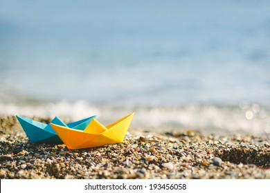 Blue and yellow paper boats on beach outdoors