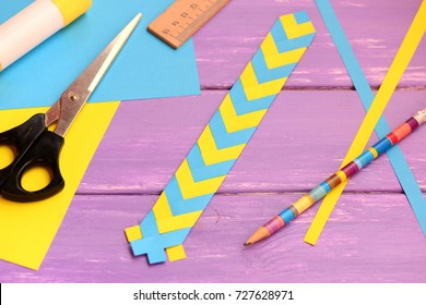Blue and yellow paper bookmark on a lilac wooden background. Simple bookmark with paper design. Stationery set on a wooden table. Closeup
