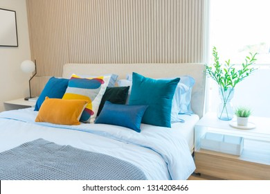 Blue and yellow pillows on bed. Bed decoration with stacked of pillows in modern bedroom.