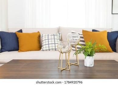 Blau-gelbe Kissen auf einem weißen Sofa mit Glasvase und Pflanzenkopf auf dem Tisch, Wohnzimmereinrichtung.