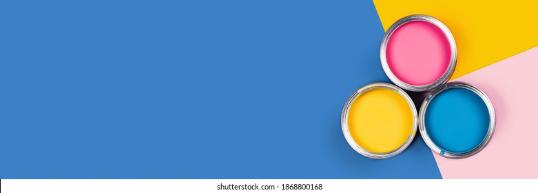 Blue, yellow, pink background with three colors paint cans. Flat lay, top view, copy space.