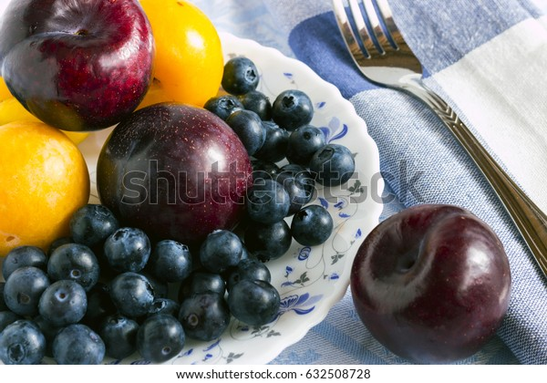 blue and yellow plums with blueberries on colored plate