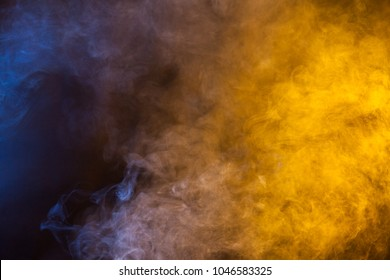 Blue and yellow smoke texture on a black background. Texture and abstract art