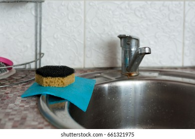 Blue and yellow stiff sponge for dishes in the sink